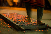 Man walking barefoot across bed of hot coals