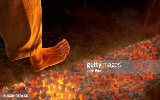 Man walking barefoot on hot coals, high angle view, close-up of foot