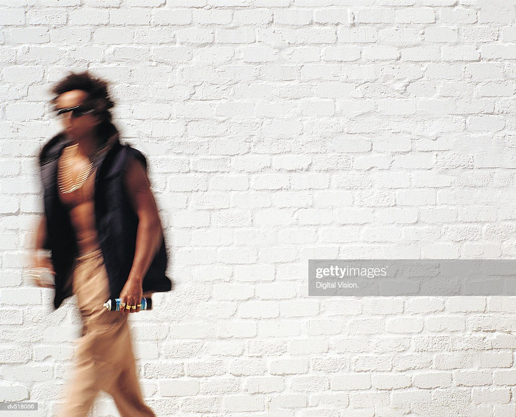 Man walking by a white wall : Stock Photo