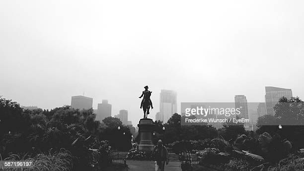 Man Walking By George Washington Monument At Garden In City Against Clear Sky