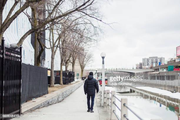 A man walking by the Rideau Canal