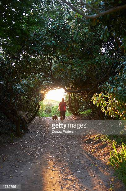 Man walking dog in countryside.