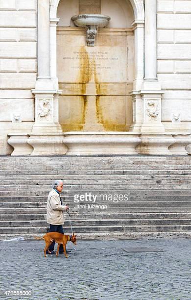 Uomo che cammina con il cane vicino fontana e passaggi in Trastevere, Roma