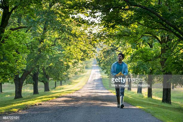 A man walking down a tree lined path.