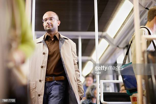 Man Walking Down Aisle on Subway