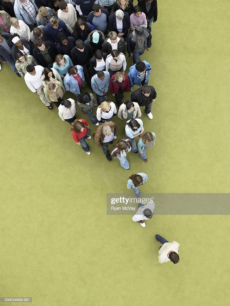 Man walking, followed by gradually increasing crowd, overhead view : Stock Photo
