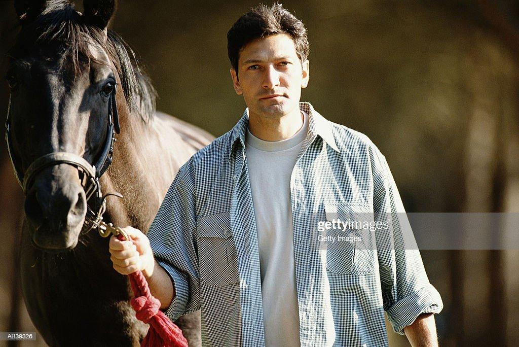Man walking horse by bit : Stock Photo