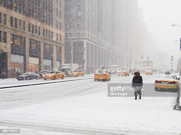 Man walking in a city in the snow during a blizzard, yellow taxis on the street.