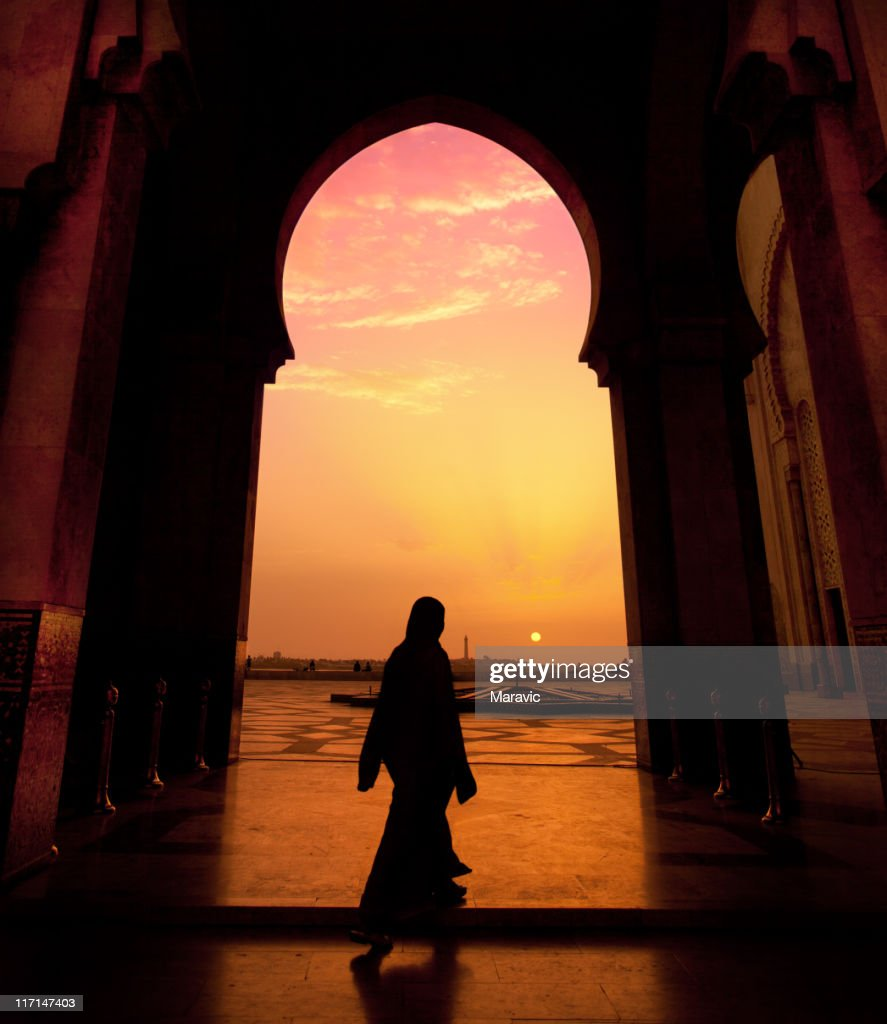 A man walking in a mosque during a sunset : Stock Photo