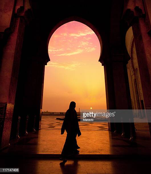 A man walking in a mosque during a sunset