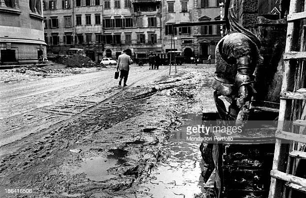 A man walking in a street covered with the mud caused by the flood of the Arno River Florence November 1966