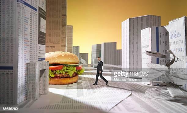 Man walking in city made of newspaper