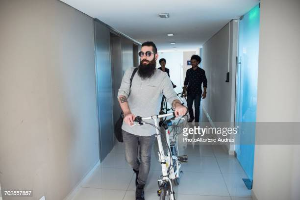 Man walking in corridor with bicycle