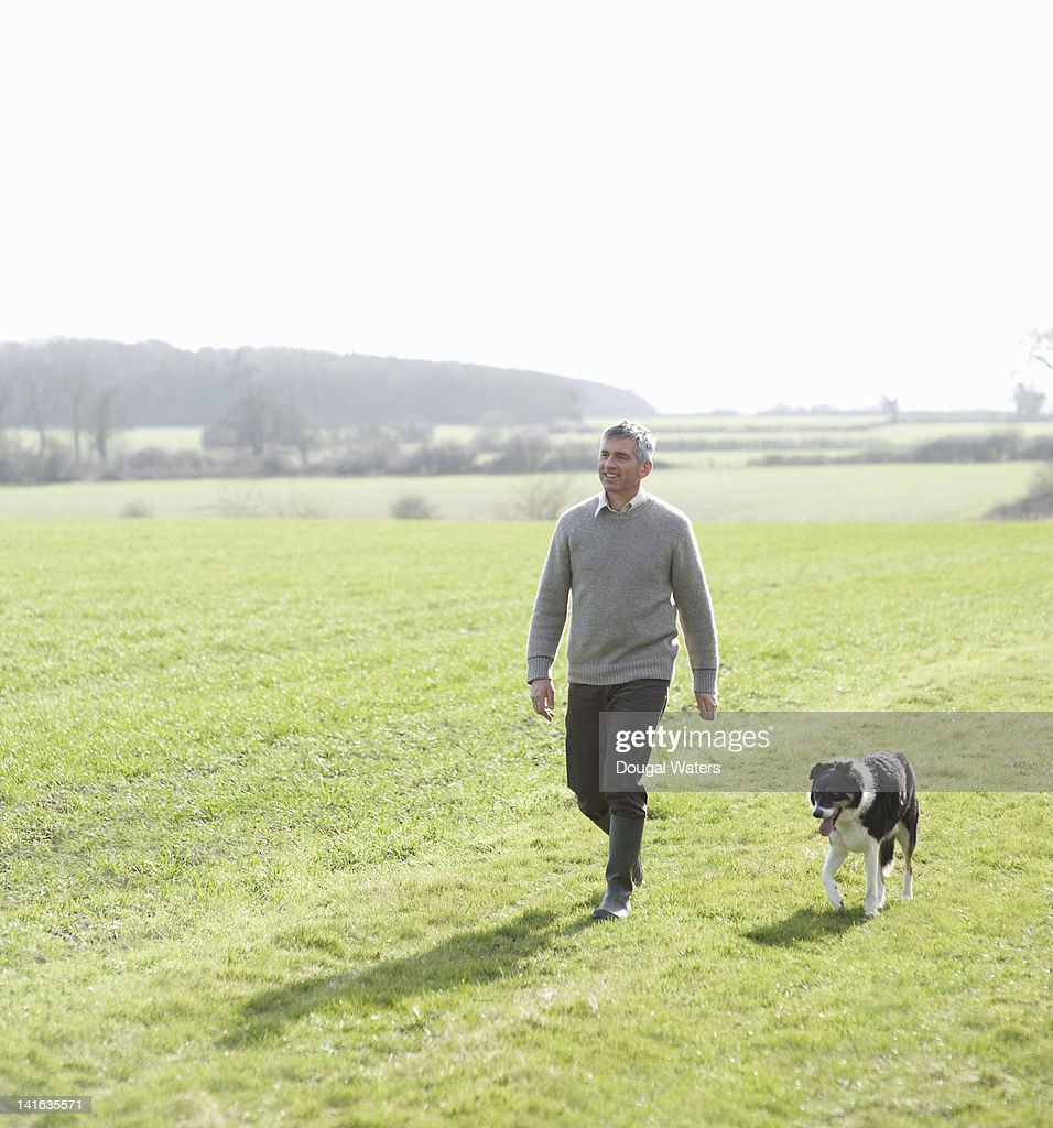 Man walking in countryside with pet dog : Photo