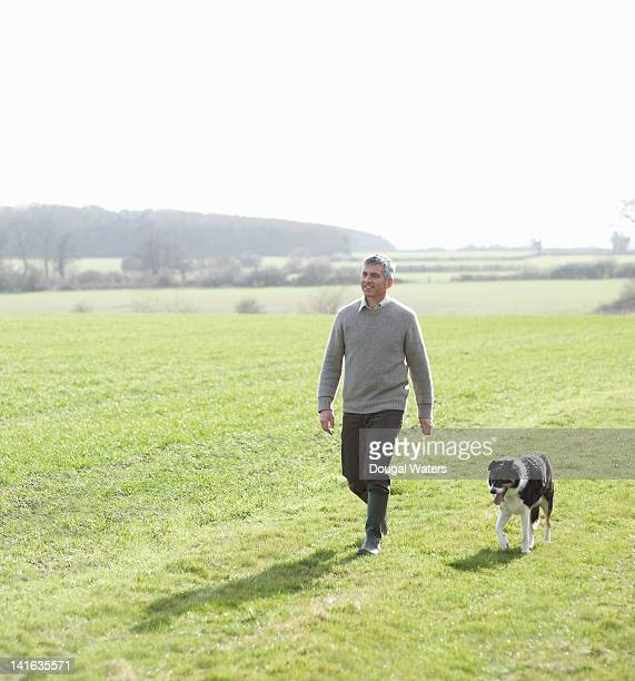 Man walking in countryside with pet dog