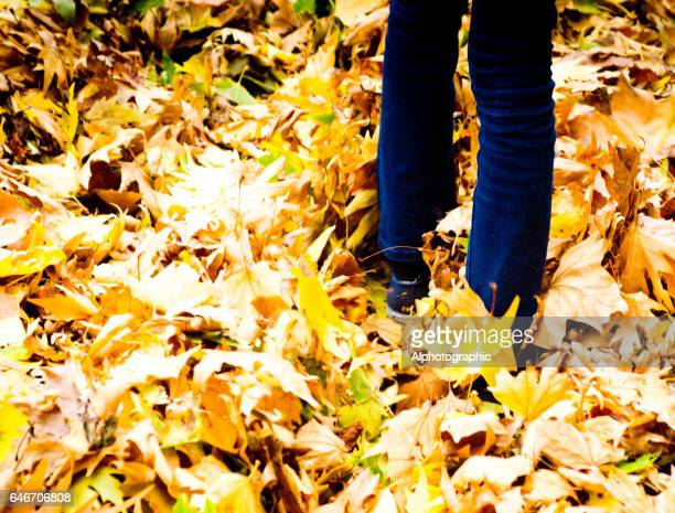 Man walking in fallen leaves