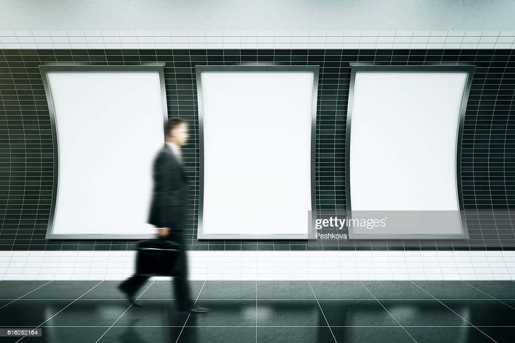 Man walking in front of posters : Foto de stock
