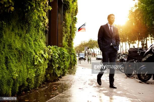 Man walking in front of vertical garden