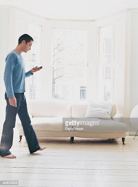 Man Walking in his House and Checking his Text Messages
