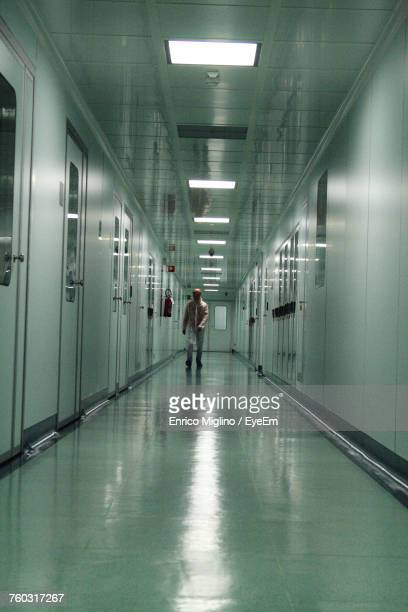 Man Walking In Illuminated Corridor