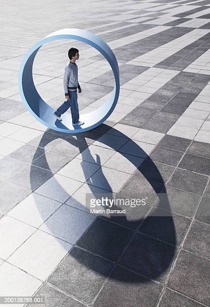 Man walking in large wheel outdoors
