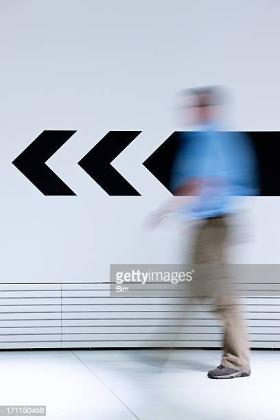 Man walking in opposite direction of arrow