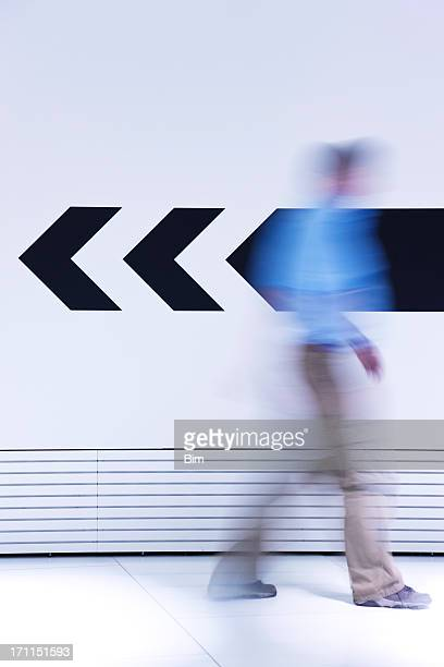 Man walking in opposite direction of arrow