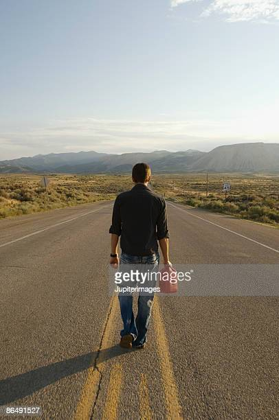 Man walking in road with gas can