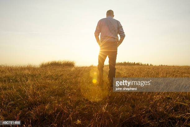 Man walking in the countryside looking at the sunset