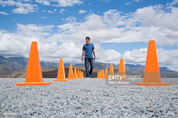 Man walking in-between two rows of safety cones