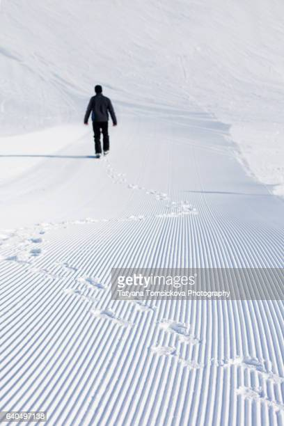 Man walking, making foot prints in the snow, snow lines made by a snow machine on a ski slope