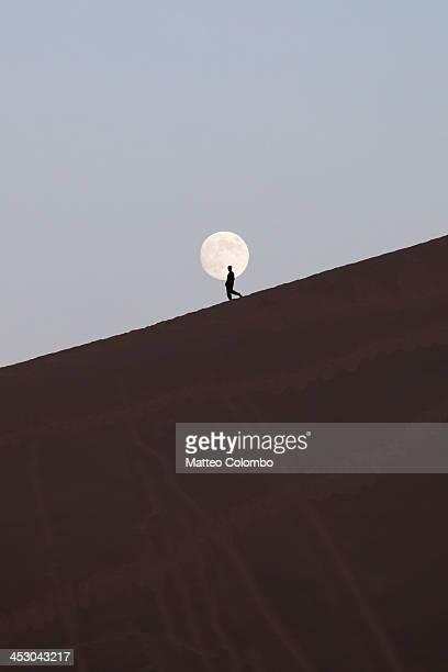 Man walking on a desert dune in front of full moon
