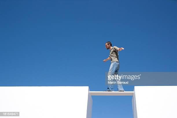 Man walking on board between two walls outdoors