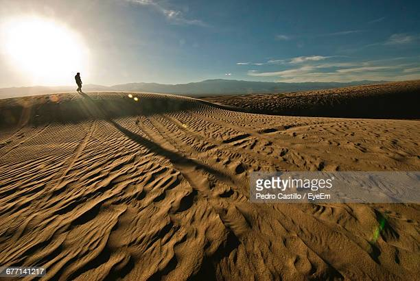 Man Walking On Desert During Sunny Day