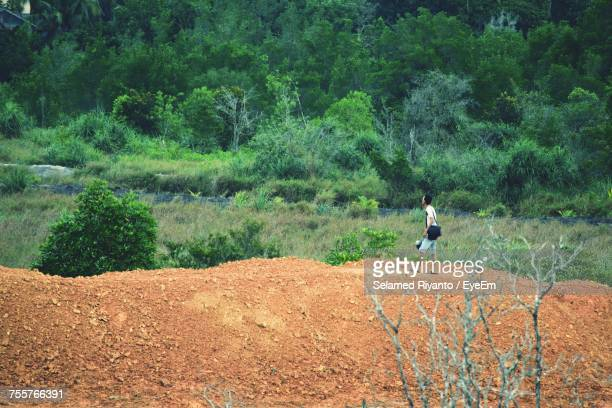 Man Walking On Footpath Against Trees At Forest