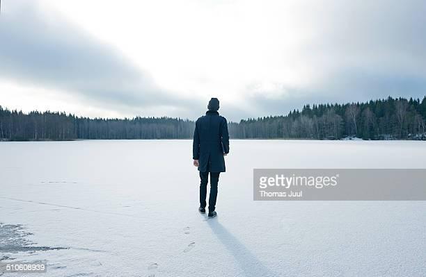 Man walking on frozen lake with laptop