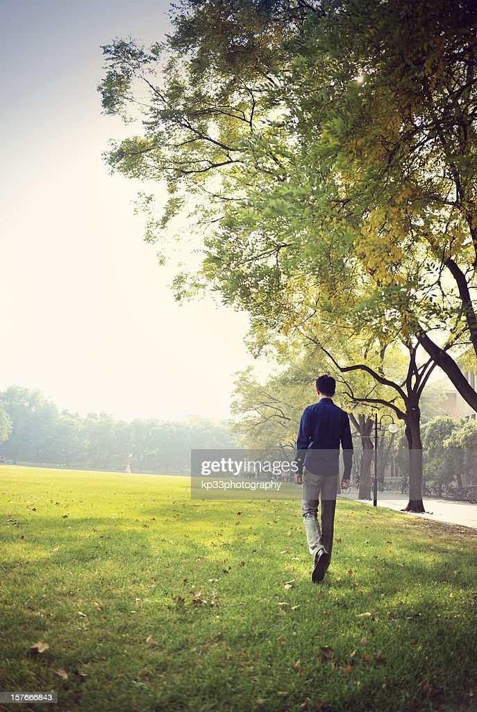 man walking on grassland : Stock Photo