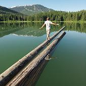 Man walking on log protruding into lake, rear view