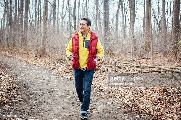 Man Walking On Path Through Forest Smiling