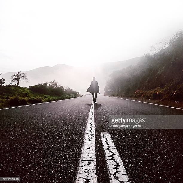 Man Walking On Road In Front Of Mountains Against Sky During Foggy Weather