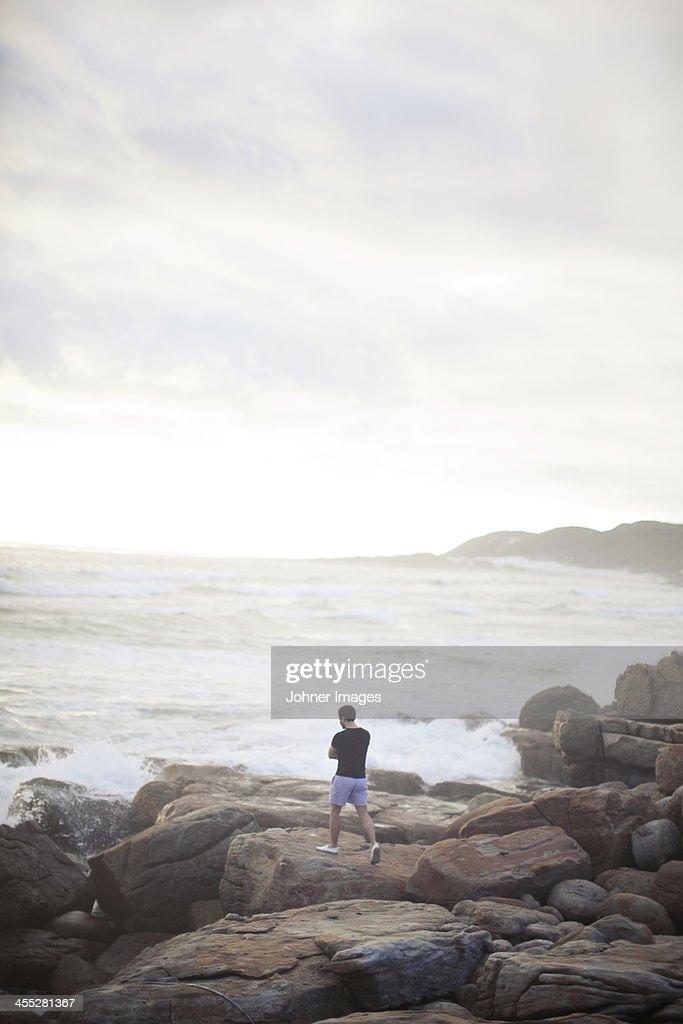 Man walking on rocky beach, Cape of Good Hope