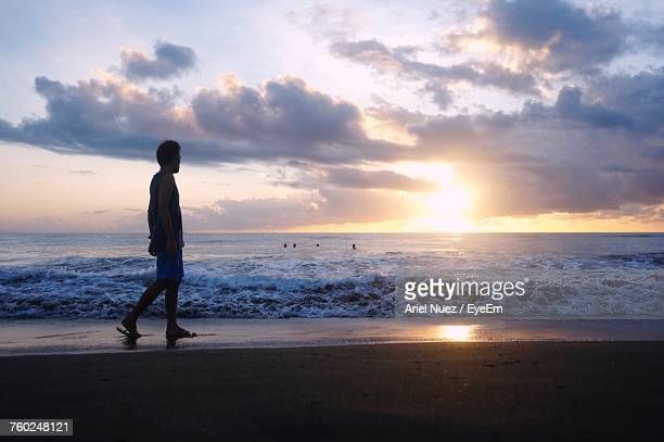 Man Walking On Shore By Sea During Sunset