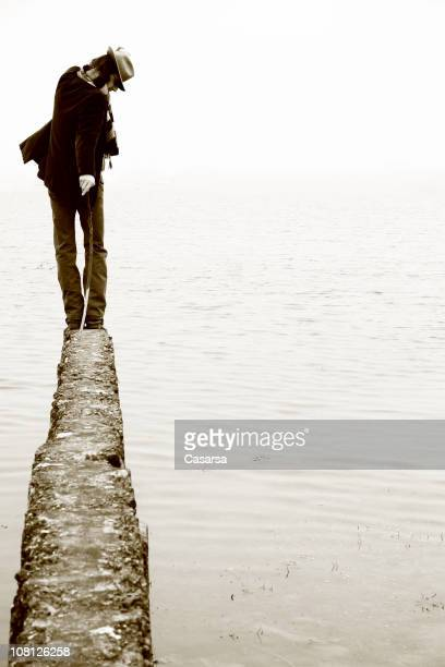 Man Walking on Skinny Ledge Looking Out Over Water