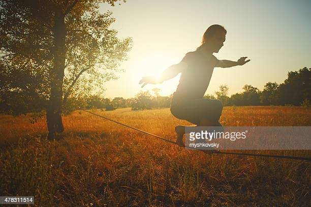 Man walking on slackline in the meadow at sunset.