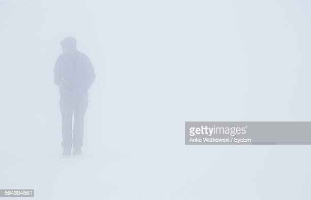 Man Walking On Snow Covered Field During Foggy Weather