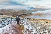 Man walking on snowy hills in Wales. Adult man hiking in winter, hills covered in snow and mist on background. Wanderlust, nature and exploration concepts.