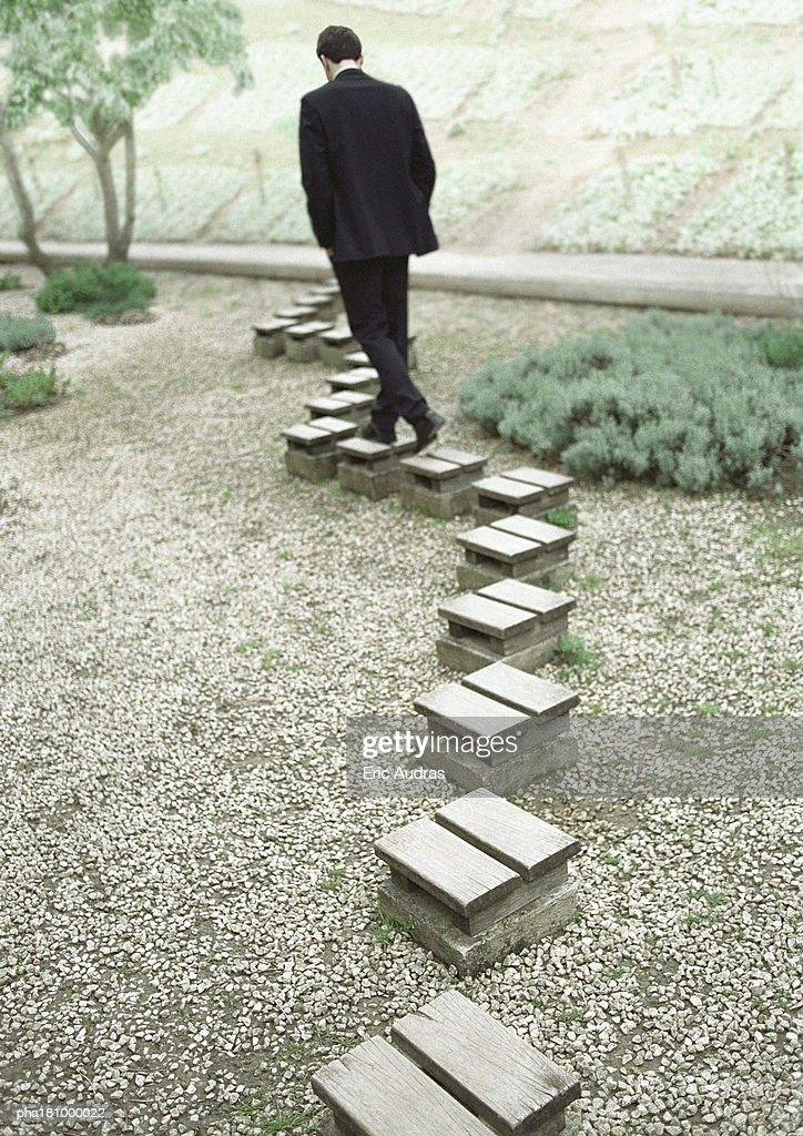 Man walking on stepping stones, rear view