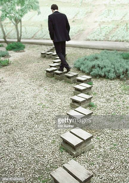 Man walking on stepping stones, rear view
