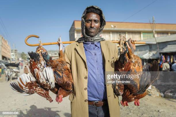 Man walking on the streets of a market transporting four cocks hanging from his walking stick