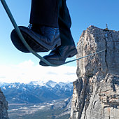 Man walking on tightrope between rock cliffs, mountains in backgrounds, close-up, low section